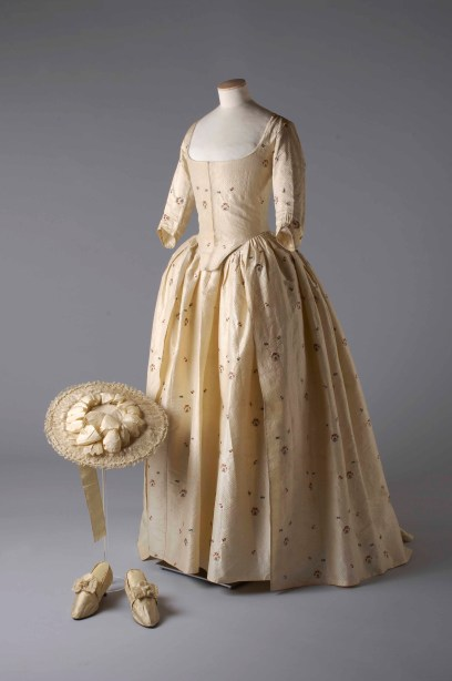 Silk_brocade_gown_hat_and_shoes_1780._Image_reproduced_by_kind_permission_of_the_Olive_Matthews_Collection_Chertsey_Museum._Photograph_by_John_Chase
